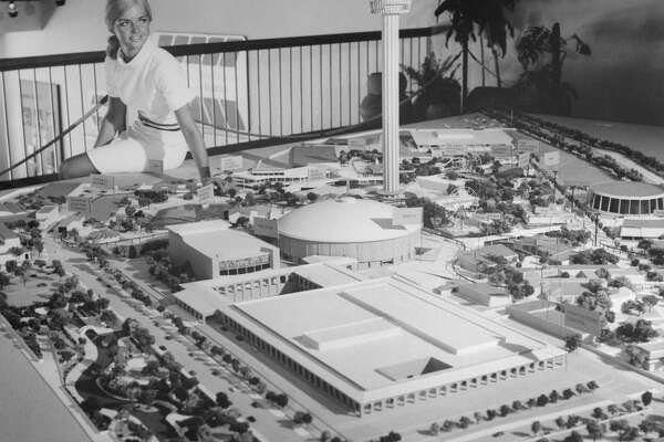 (Original Caption) The official 1968 World's Fair in miniature is viewed here at Hemisfair's exhibit showroom on the fair site in San Antonio, Texas, by attractive Patty Poulsen. The tall structure in the center is the Tower of the Americas, Hemisfair's 622 foot theme structure with a rotating restaurant, observation decks and high speed outside elevators. The domed structure at right is the U.S. Government's Confluence Theatre, which will feature a special 20-minute film by Academy Award winner Francis Thompson. The three large buildings in the foreground area the San Antonio Civic and Convention Center at Hemisfair.