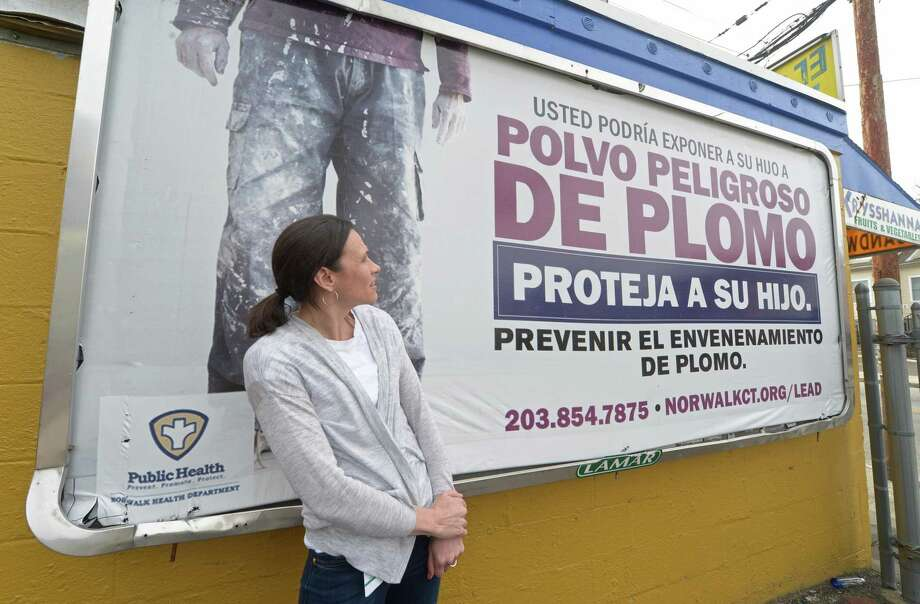 Norwalk Health Department Lead Poisoning Prevention and Control Program Associate Nora Llach stands with one of the billboards at 112 South Main Street which is part of a campaign directed at the children of house painters Tuesday, March 27, 2018 in Norwalk, Conn. Norwalk has halved the population under 6 years of age with lead poisoning in two years -- in part by visiting the homes of every active lead poisoning case. Photo: Erik Trautmann / Hearst Connecticut Media / Norwalk Hour