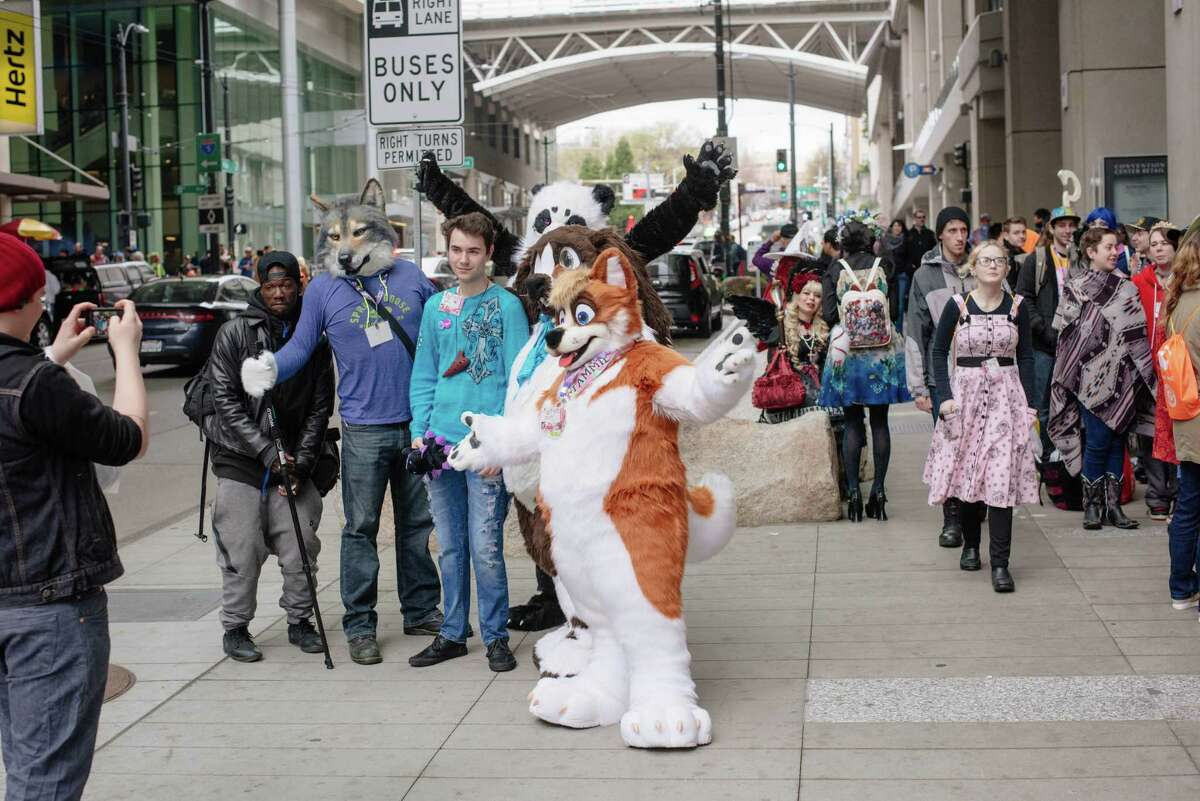 FILE - Furries take a photo with a fan outside the Washington State Convention Center during Sakura-Con on Sunday, April 1, 2018.