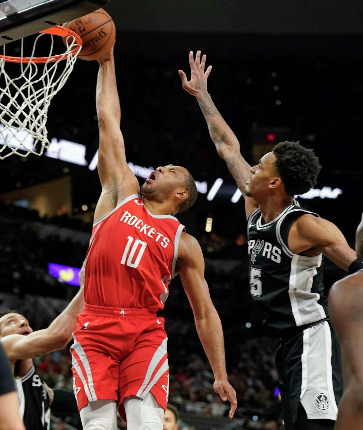 Houston Rockets' Eric Gordon (10) shoots against San Antonio Spurs' Dejounte Murray during the first half of an NBA basketball game, Sunday, April 1, 2018, in San Antonio. (AP Photo/Darren Abate)