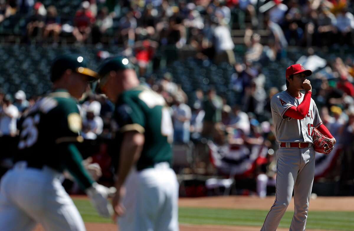 Shohei Ohtani (17) stands on the mound as third base coach Matt Williams high fives Matt Chapman (26) after Chapman hit a three-run homerun in the second inning as the Oakland Athletics played the Los Angeles Angels of Anaheim at the Oakland Coliseum in Oakland, Calif., on Sunday, April 1, 2018.