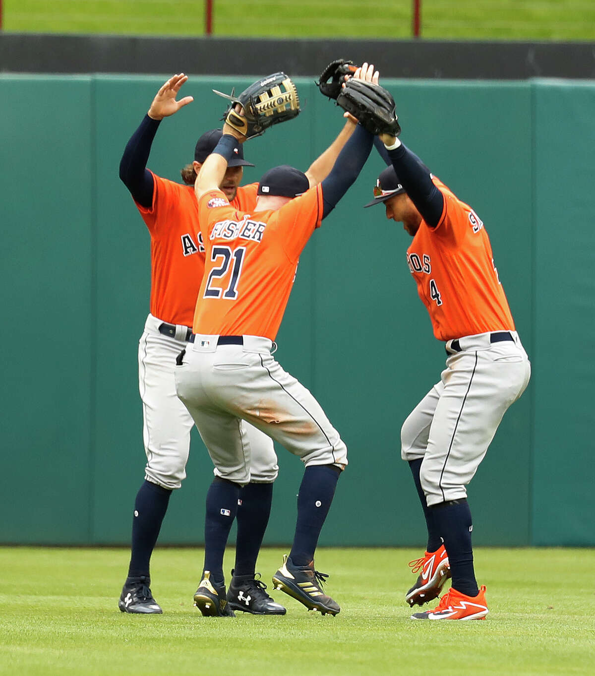 Houston Astros George Springer (4), Derek Fisher (21), and Jake Marisnick (6) celebrate their 8-2 win over the Texas Rangers after an MLB baseball game at Globe Life Park, Sunday, April 1, 2018, in Arlington.