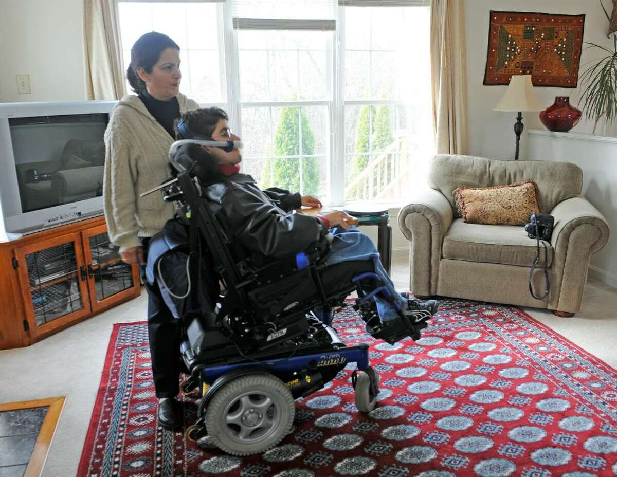 Daisy Munshi cares for her son Sachin Munshi at their home in Delmar, New York November 24, 2009. Sachin Munshi lives with Duchenne's Muscular Dystrophy and will graduate with a Bachelor of Science Degree from the University at Albany on December 6th. (Skip Dickstein/Times Union)
