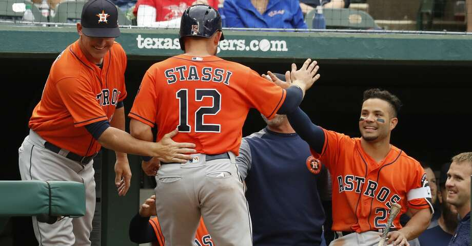 Houston Astros Max Stassi (12) celebrates with Jose Altuve and manager AJ Hinch (14) after scoring a run on Derek Fisher's triple in the fifth inning of an MLB baseball game at Globe Life Park, Sunday, April 1, 2018, in Arlington.   ( Karen Warren / Houston Chronicle ) Photo: Karen Warren/Houston Chronicle