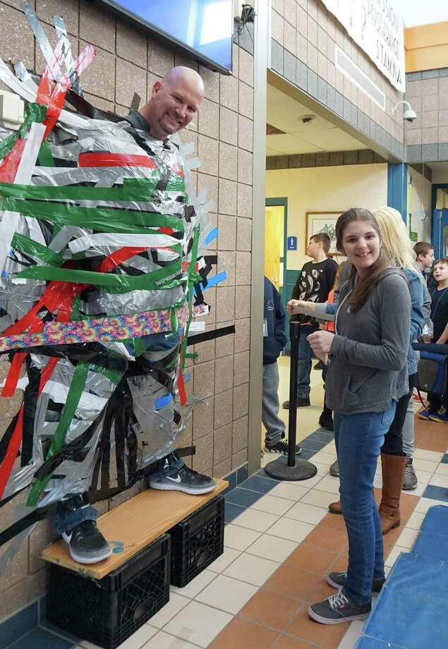 On March 16, Cairo-Durham Middle School Principal Michael Mitchell, seen here with eighth-grader Rielli Webner, volunteered to be ?stuck for a buck? to help raise money for the school?s annual Pennies for Patients fundraiser. During lunches, middle school students and staff could donate $1 for a piece of duct tape and use it to stick Mitchell to the wall. More than $400 was collected in one afternoon. Cairo-Durham Elementary also participates in the annual Pennies for Patients fundraiser.