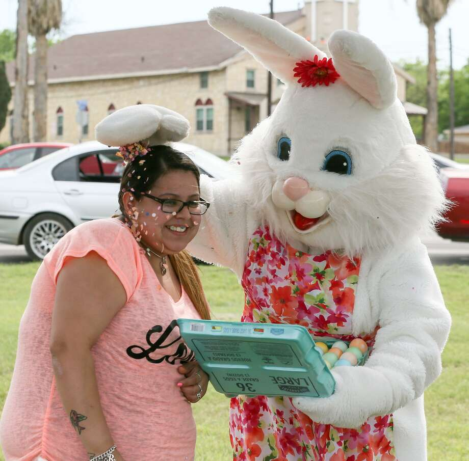Claudia Santos, dressed as the Easter Bunny, cracks a cascarone on Rosalie Castellanos's head while spreading Easter cheer by visiting family campsites at Woodlawn Lake Park on Sunday, April 1, 2018.  MARVIN PFEIFFER/mpfeiffer@express-news.net Photo: Marvin Pfeiffer, Staff / San Antonio Express-News / Express-News 2018