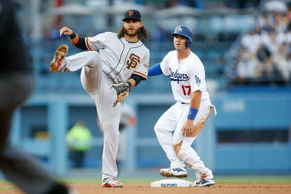San Francisco Giants shortstop Brandon Crawford, left, watches as his throw to first base is late after forcing out Los Angeles Dodgers' Kyle Farmer, right, during the third inning of a baseball game Sunday, April 1, 2018, in Los Angeles. (AP Photo/Danny Moloshok)