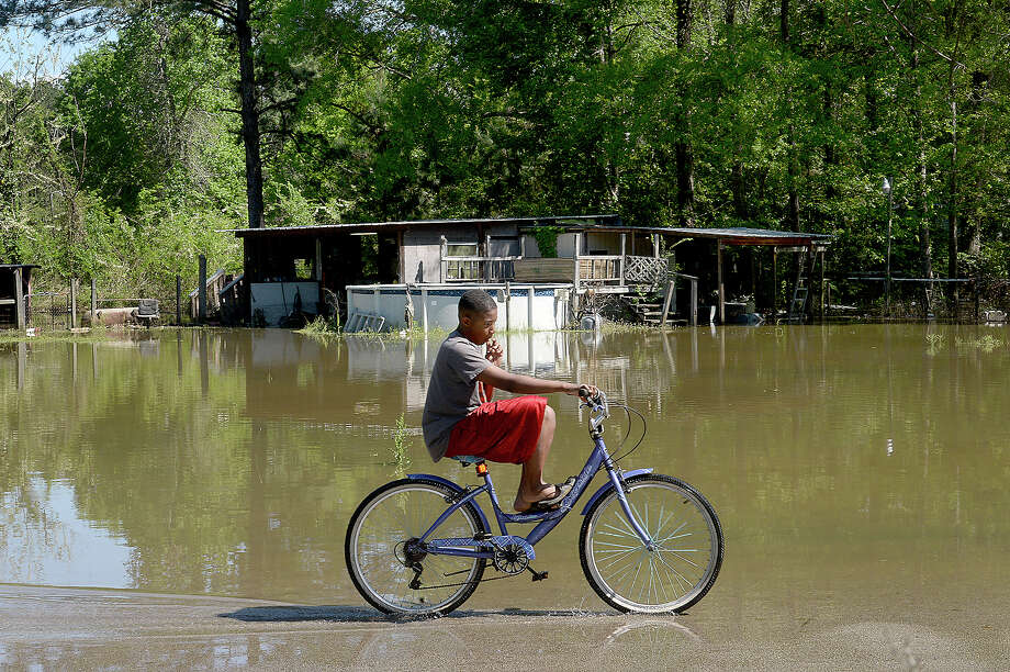"""Demarcus Dean, 12, rides his bike through his flooded neighborhood in Bon Wier Friday. Many residents of the area known as """"The Hole"""" evacuated Thursday as rising waters quickly flooded yards and roadways, nearing entry levels at some elevated homes. Heavy rainfall and the opening of the dams at Toledo Bend have swelled the Sabine River, area creeks and ditches and is expected to rise further through the weekend. Photo taken Friday, March 30, 2018 Kim Brent/The Enterprise Photo: Kim Brent / BEN"""