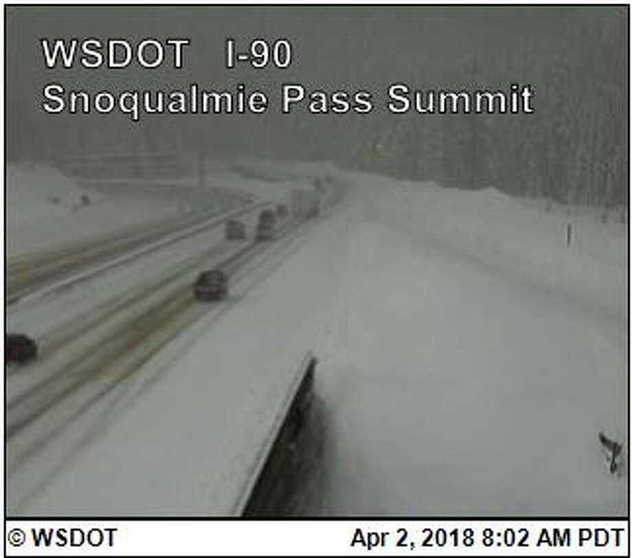The first traffic on Monday travels over a snowy I-90 over Snoqualmie Pass. The pass was closed overnight after multiple crashes including one that left a pregnant woman dead. Photo: WSDOT