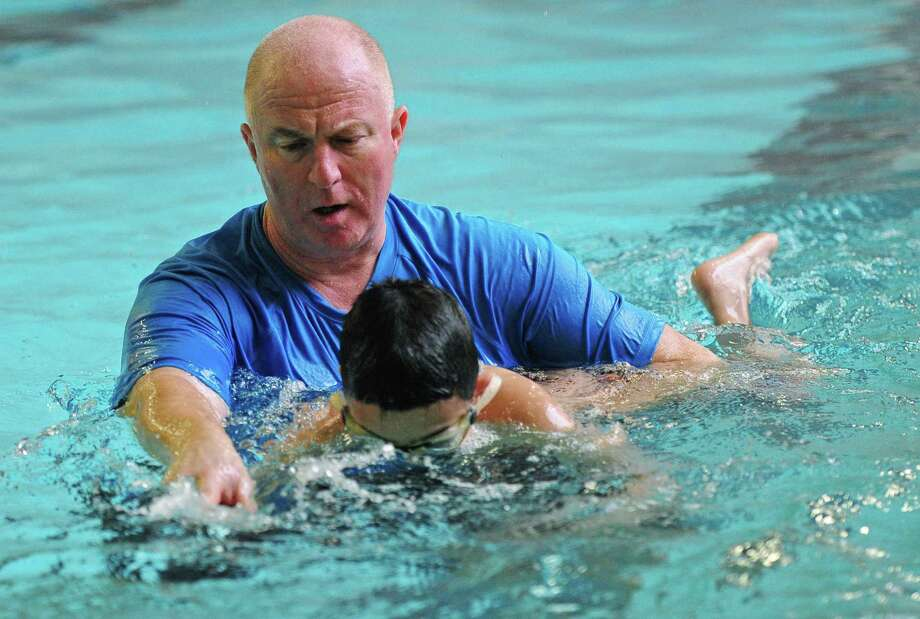 Norwalk High School Athletic Director Doug Marchetti teaches swimming to autistic children as part of a special program at the high school's pool Tuesday, March 20, 2018, in Norwalk, Conn. Photo: Erik Trautmann / Hearst Connecticut Media / Norwalk Hour