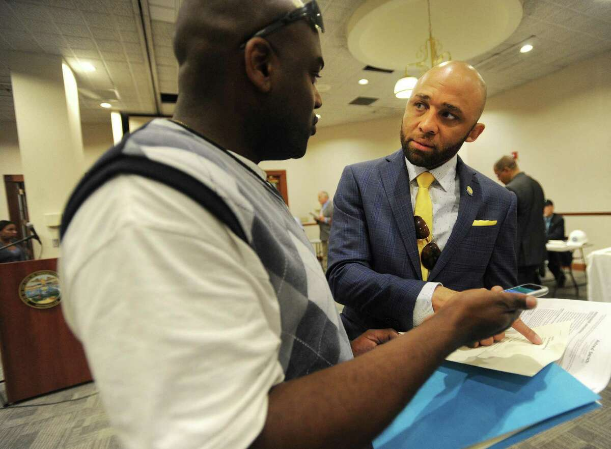 Chris Irby, left, of Bridgeport, gets advice on his resume from Bridgeport Director of Re-Entry Affairs Louis Reed at the Bridgeport Re-Entry Career Fair, at the Margaret Morton Government Center in Bridgeport, Conn., on June 28, 2017.