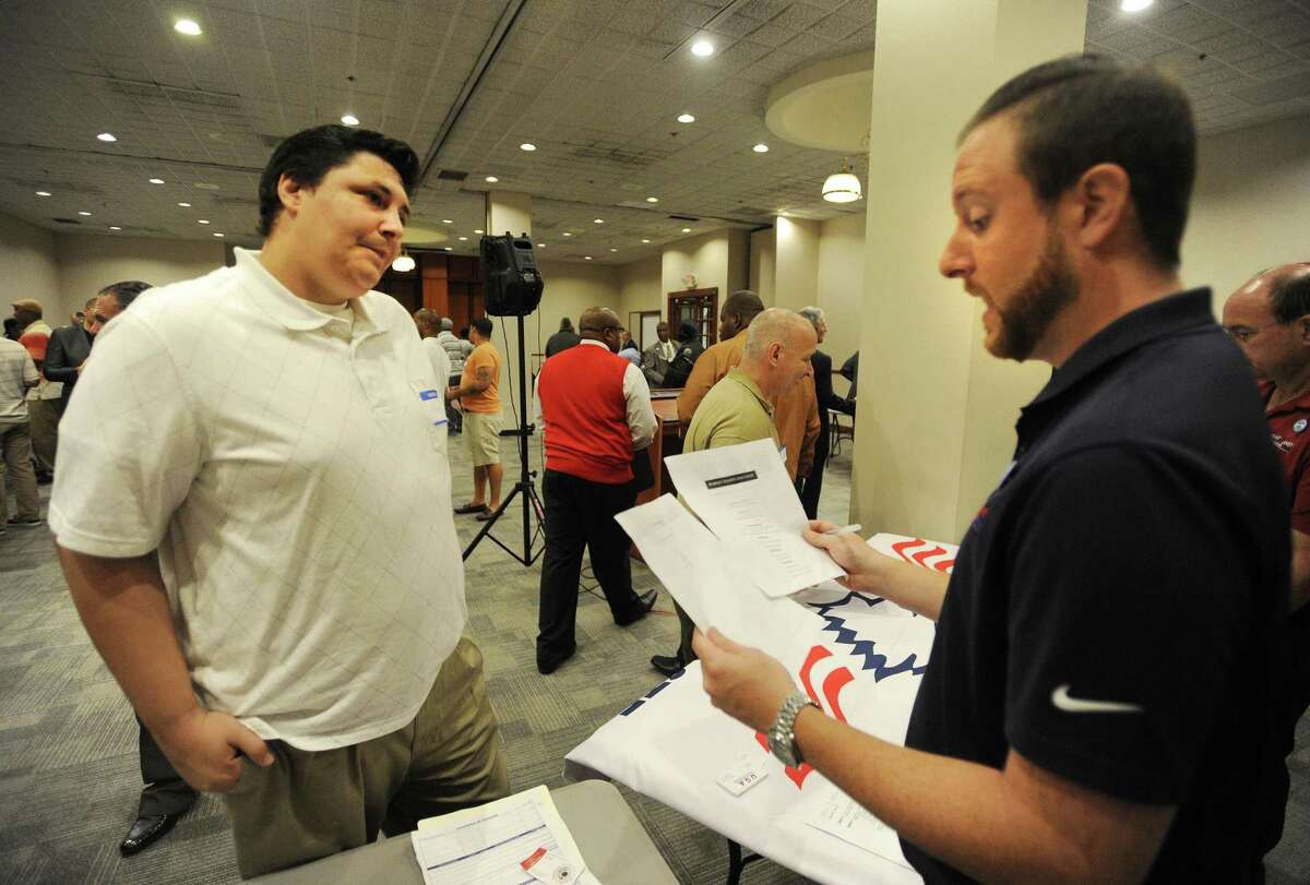 Robert Daccolti, left, of Bridgeport, gives his resume to Mike Lauro, of All American Waste, at the Bridgeport Re-Entry Career Fair, at the Margaret Morton Government Center in Bridgeport, Conn., on June 28, 2017.