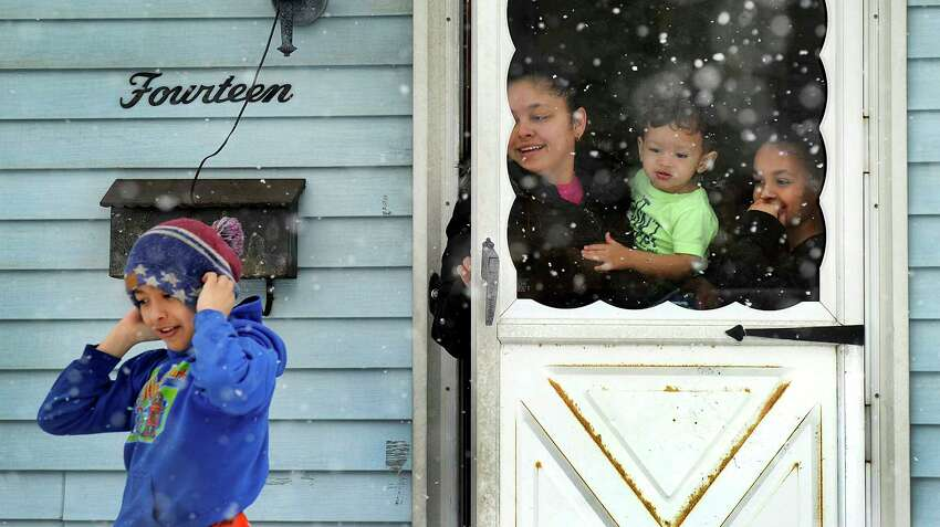 Sandy Velez, with three of her kids, Brandon, left, Angel and Joselyn, watch the snow falling at their Germantown Road home in Danbury Monday, April 2, 2018. Danbury kids had a snow day. Some area downs had a delay opening.