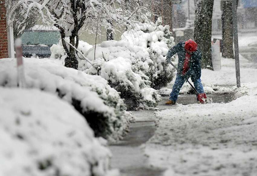 A man shovels a sidewalk in downtown Danbury during a snowfall that started early in the morning, Monday, April 2, 2018.