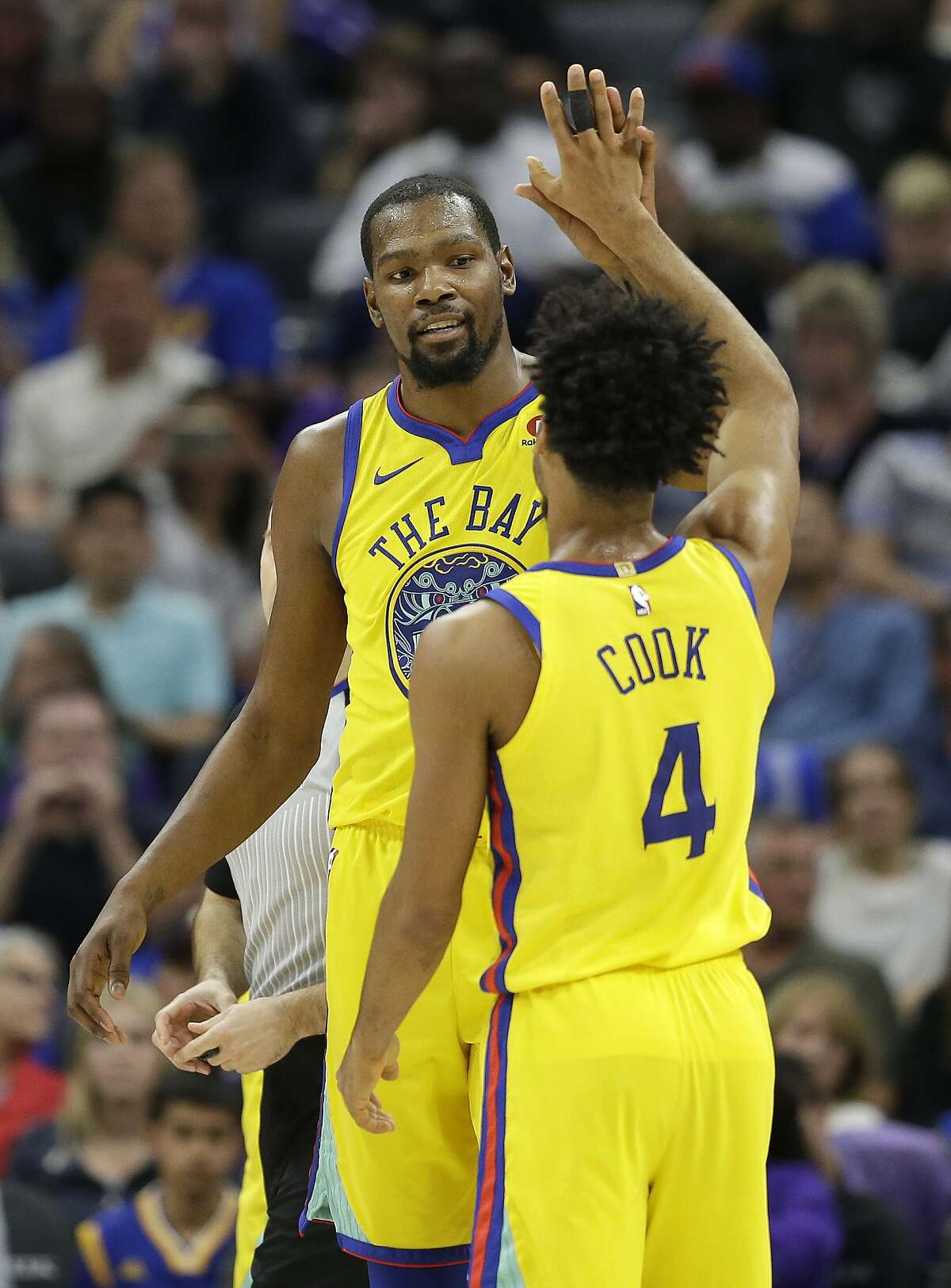 Golden State Warriors forward Kevin Durant gets a high five from teammate Quinn Cook after scoring against the Sacramento Kings during the second half of an NBA basketball game Saturday, March 31, 2018, in Sacramento, Calif. The Warriors won 112-96.