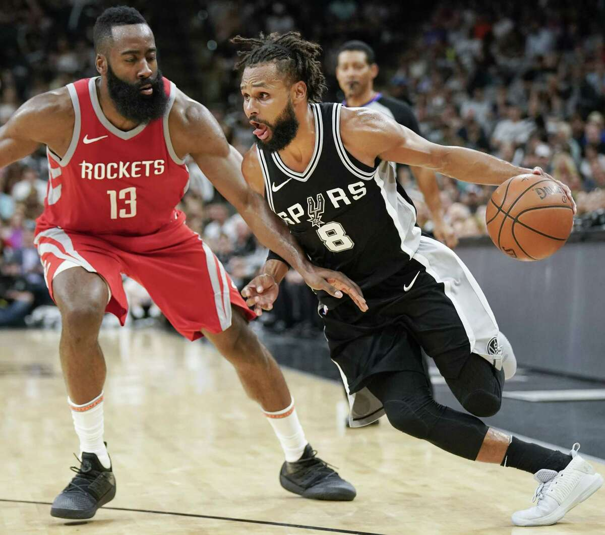 San Antonio Spurs' Patty Mills (8) drives against Houston Rockets' James Harden during the second half of an NBA basketball game Sunday, April 1, 2018, in San Antonio. San Antonio won 100-83. (AP Photo/Darren Abate)