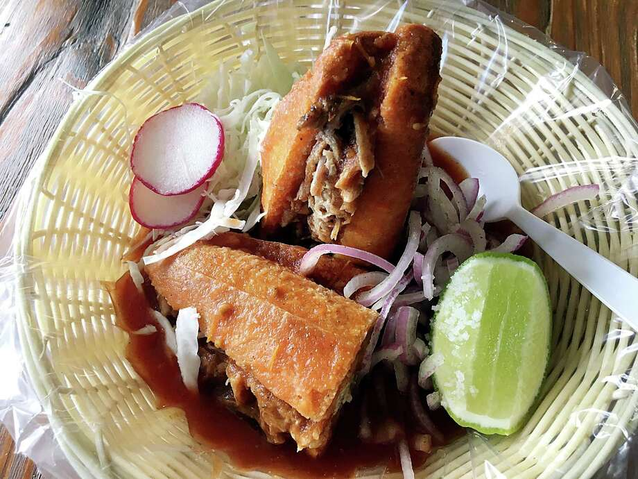 "The torta ahogada at Ro-Ho Pork & Bread is a ""drowned"" sandwich that starts with a handmade roll that's crispy outside, fluffy inside. It's stuffed with juicy, mild carnitas, then drenched with a thin achiote broth. Photo: Mike Sutter /Staff"