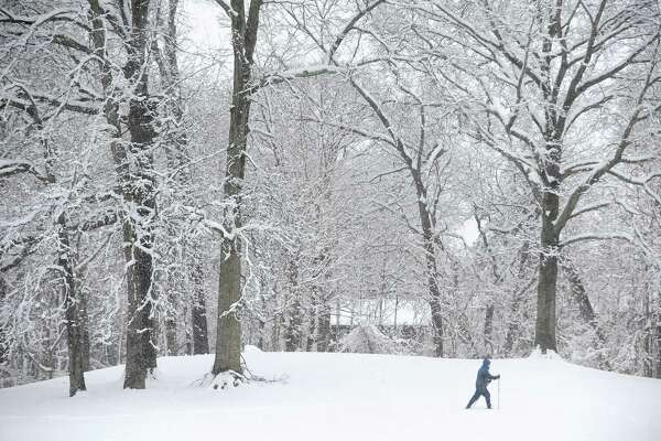 27-year-old Julie Arduini, of Stamford, snowshoes around Scalzi Park during the early morning snow in downtown Stamford, Conn. on Monday, April 2, 2018.