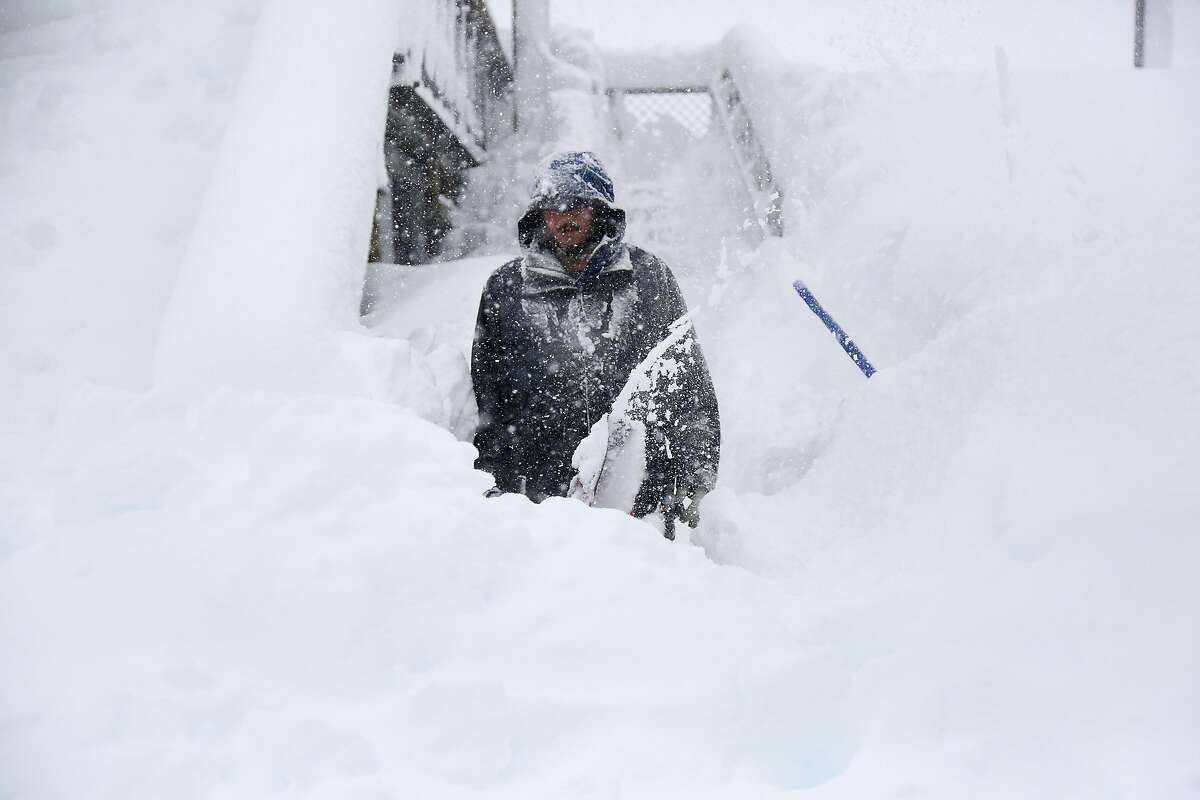 In this photo provided by Northstar California, a resort employee clears a path covered in snow at the top of Zephyr Express Chairlift Thursday, March 22, 2018, in Truckee, Calif. A powerful storm spread more rain across California on Thursday, flooding streets and threatening to unleash mud and debris flows into communities near areas burned bare by wildfires.