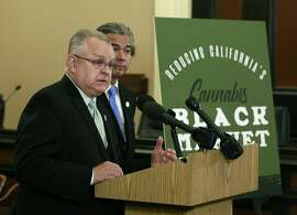Assemblyman Tom Lackey, R-Palmdale, discusses the measure he and Assemblyman Rob Bonta, D-Oakland, right, are proposing to cut taxes on legal marijuana, Thursday, March 15, 2018, in Sacramento, Calif. The lawmakers say current taxes are so high that users often find it cheaper to keep buying illegal products from the black market. (AP Photo/Rich Pedroncelli)
