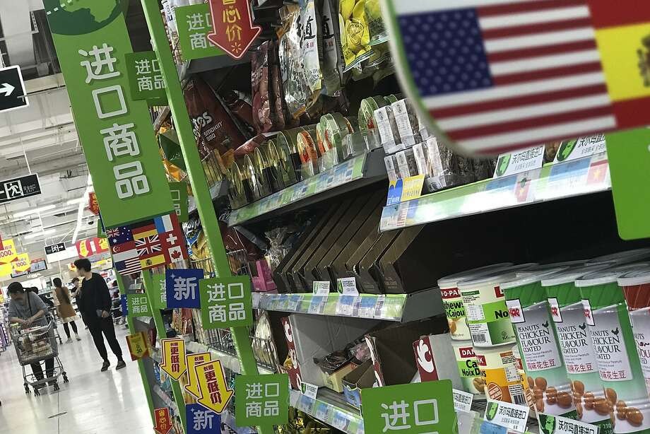 Women push a shopping cart near nuts and sweets imported from the United States and other countries displayed on a section selling imported foods at a supermarket in Beijing, Monday, April 2, 2018. China raised import duties on a $3 billion list of U.S. pork, fruit and other products Monday in an escalating tariff dispute with President Donald Trump that companies worry might depress global commerce. (AP Photo/Andy Wong) Photo: Andy Wong, Associated Press