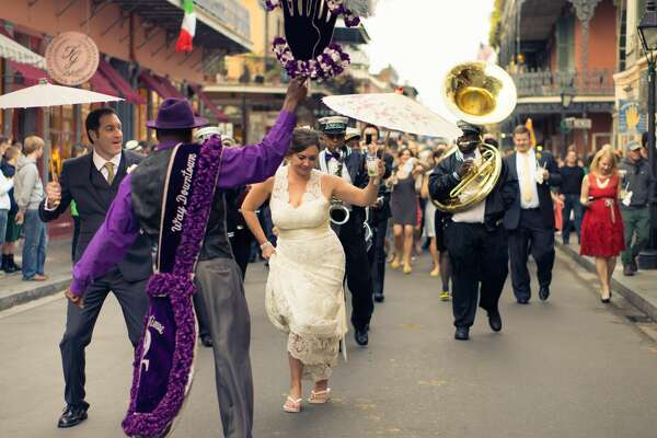 "[UNVERIFIED CONTENT] Groom and bride and the wedding party join in the procession ""second lining"" down Royal Street in the French Quarter in New Orleans."