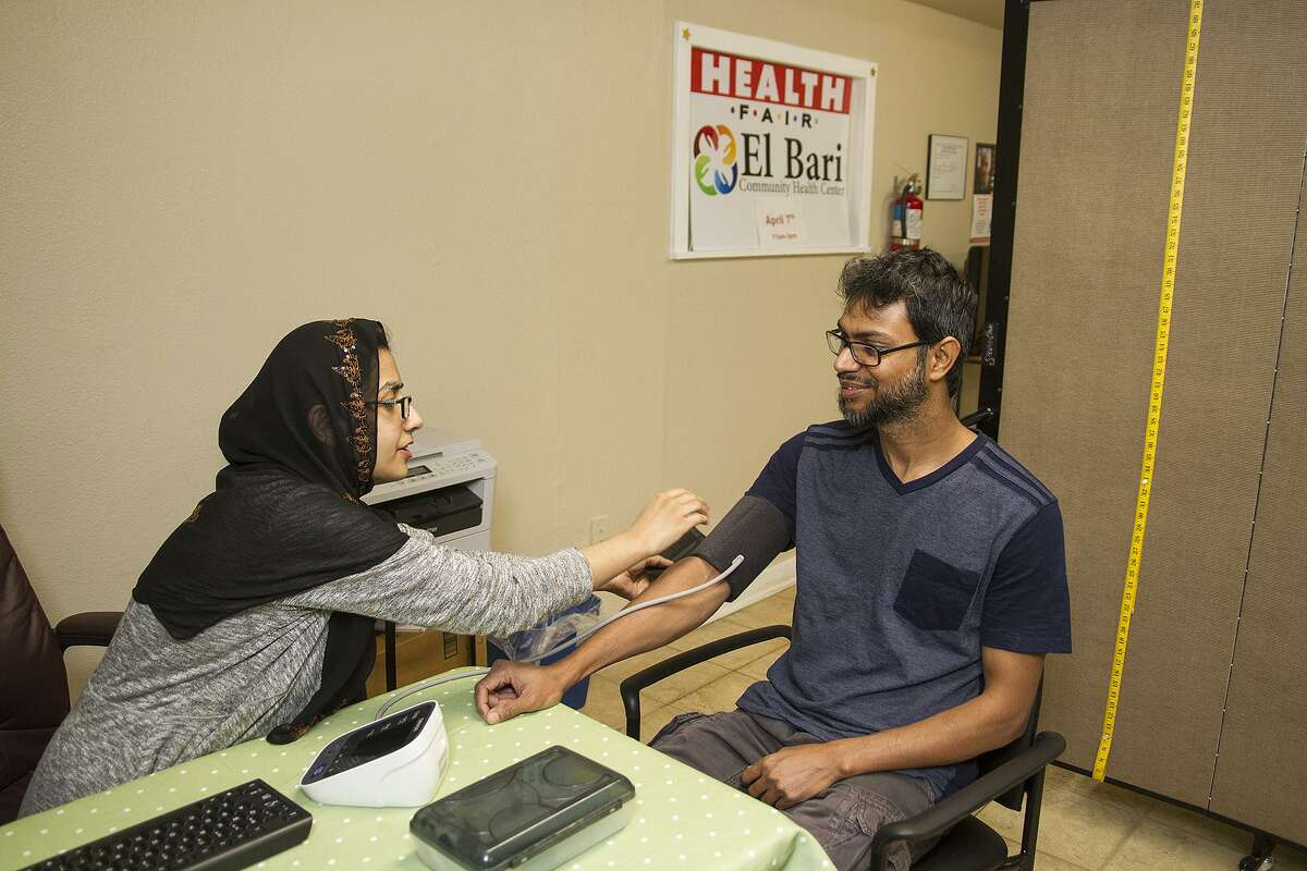 Dr. Hina Malik takes the blood pressure of patient Mohammad at El Bari Clinic, which treats patients without health insurance for free. A reader praises the facility, run by a volunteer group of physicians who are all Muslim.