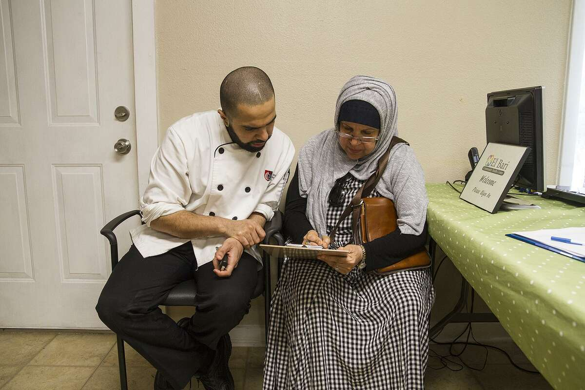 Mohammad Aldrees helps his mother, Khatoon Taher, fill out new paperwork at the clinic near De Zavala Road and Interstate 10.