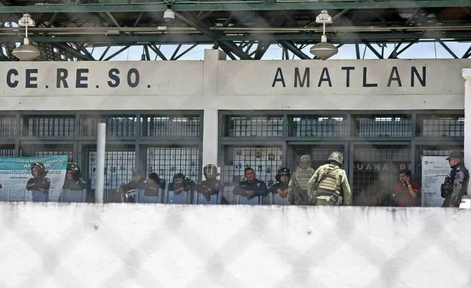 """Policemen and Mexican marines guard the entrance of """"La Toma"""" prison where on Sunday dawn a riot was registered inside with a balance of 7 policemen killed, in Amatlan de los Reyes, Veracruz State, Mexico on April 1, 2018. Seven police were killed Sunday trying to put down a riot at a prison in eastern Mexico, authorities said, the latest outburst of deadly violence in the country's jails. / AFP PHOTO / VICTORIA RAZOVICTORIA RAZO/AFP/Getty Images Photo: VICTORIA RAZO, AFP/Getty Images / AFP or licensors"""