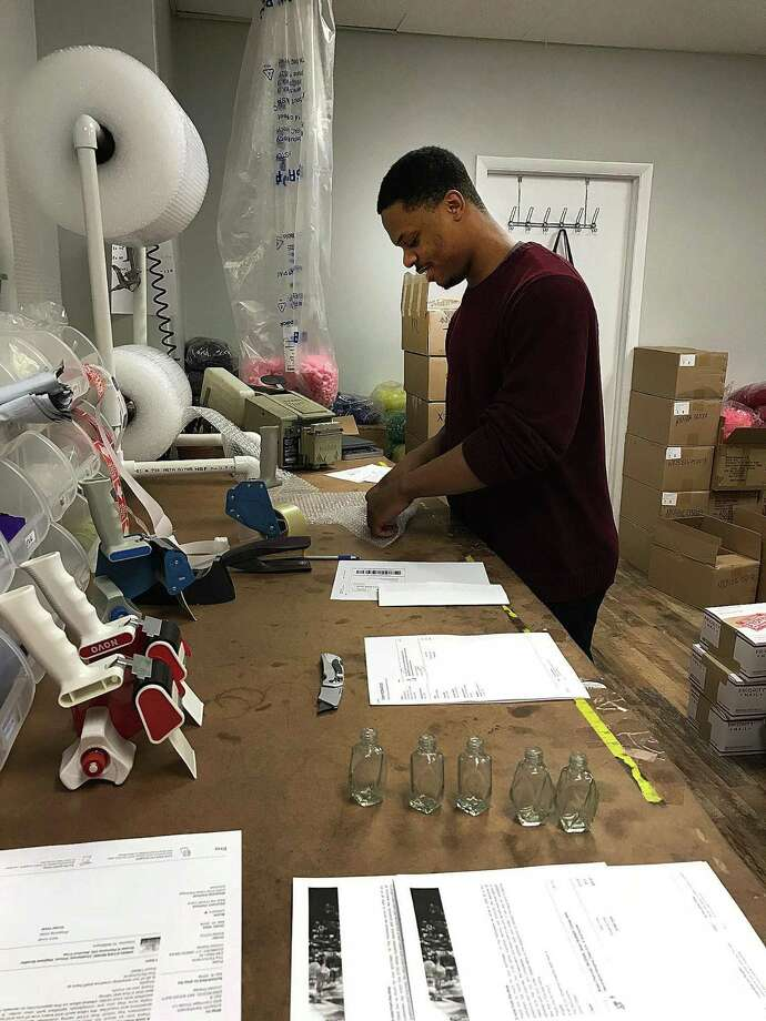 Shaquille Wright fills online orders at The Parfumerie on Main Street in Danbury, Conn., on Monday, April 2, 2018. Photo: Chris Bosak / Hearst Connecticut Media / The News-Times
