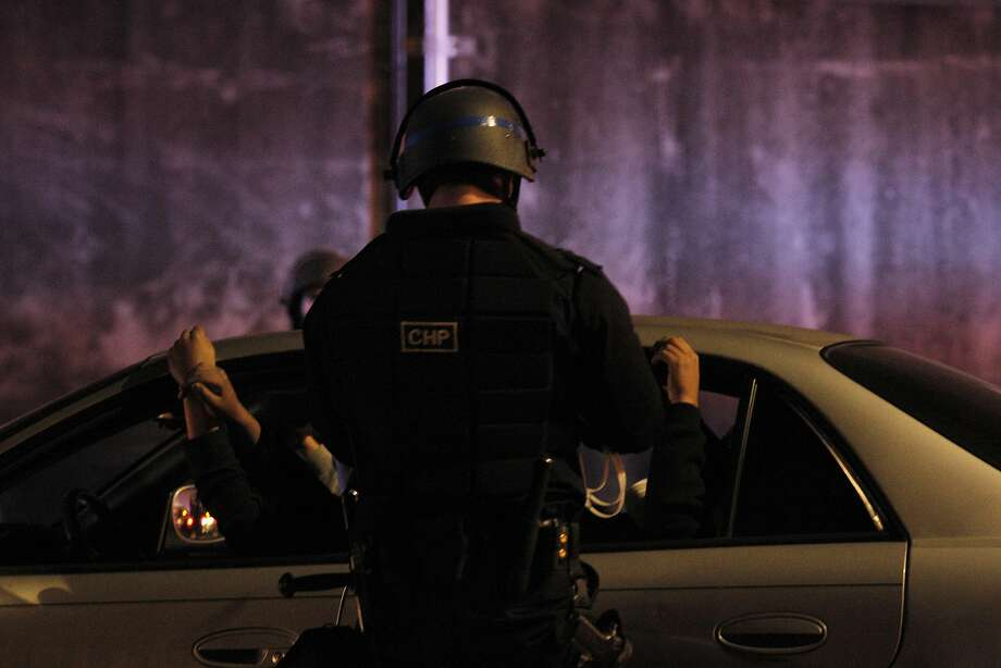 A driver  and his passengers hold their hands up while they wait to be cited after CHP, Oakland police and Alameda County sheriff's officers raided a large sideshow in 2014 on Mari time Street in Oakland. More than 100 vehicles were trapped. Photo: Carlos Avila Gonzalez / The Chronicle 2014