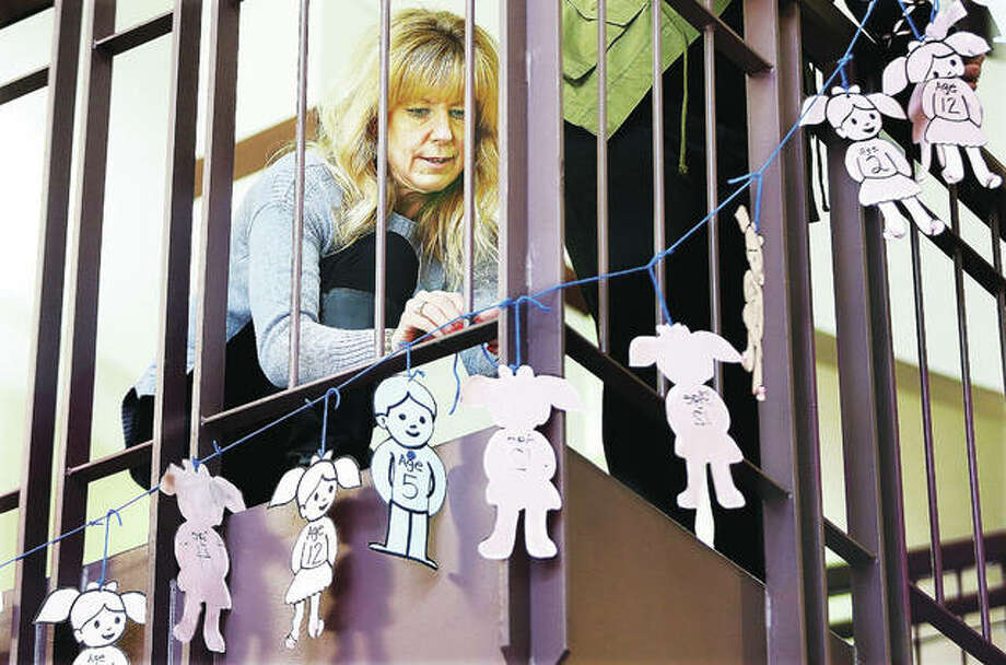 Julie Eberhart, office administrator for the Madison County Child Advocacy Center, helps hang small paper boy and girl cutouts in the Madison County Administration Building Monday in Edwardsville. Each of the paper cutouts represent one real child who has been interviewed in Madison County in connection with abuse. A ceremony will be held Friday at 10 a.m. in the administration building as part of recognizing Child Abuse Prevention Month. Photo: John Badman | The Telegraph