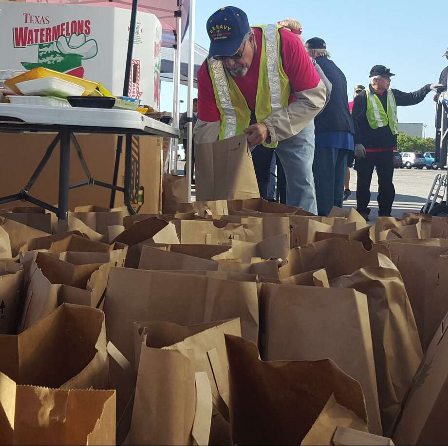 Baldemar Garcia, a U.S. Navy veteran, loads food into dozens of grocery bags supplied by local food banks for Soldiers' Angels. Photo: Jeff B. Flinn / Northeast Herald