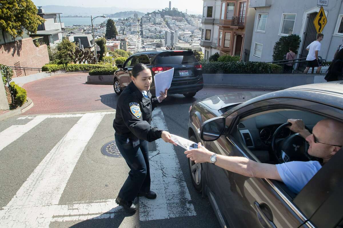 On Lombard Street, cadet Jessica Banuelos passes out a flyer to Mark Chiarucci of Moraga. The leaflet alerts drivers to take valuables with them.