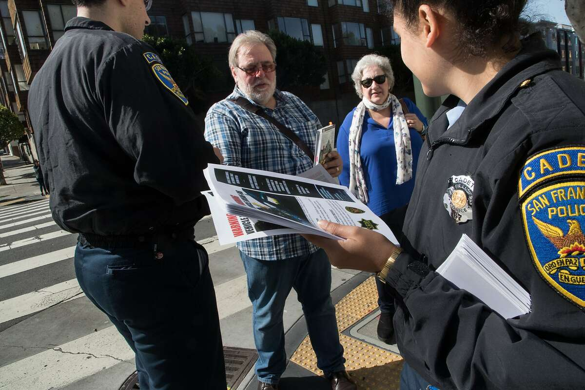 David and Vicki Woosey of the UK receives a flyer from SFPD cadets Ibrahem Abukhdeir and Sophia Abarca to leave nothing in their cars on Monday, April 2, 2018 in San Francisco, CA.