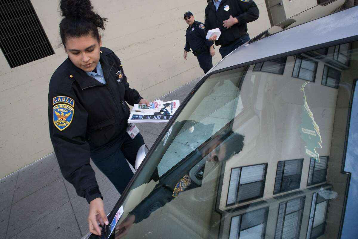 SFPD cadet Sophia Abarca with cadet Ibrahem Abukhdeir and SFPD Officer Michael Amoroso (middle) leaving flyers on windshields to help convince everybody to leave nothing in their cars on Monday, April 2, 2018 in San Francisco, CA.