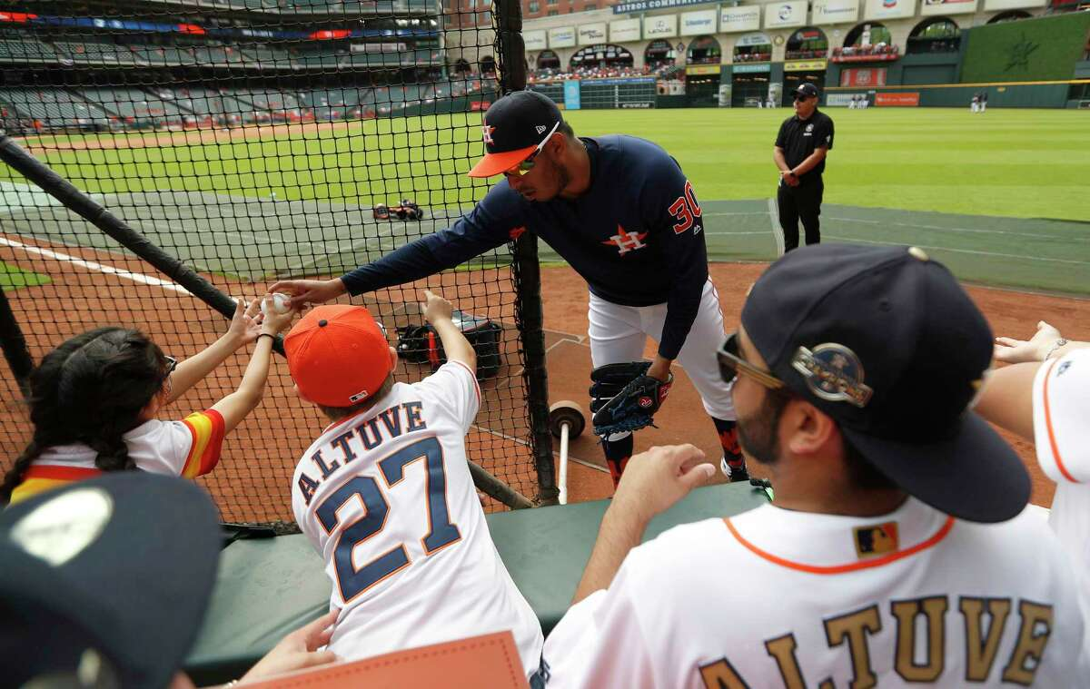 Houston Astros relief pitcher Hector Rondon (30) hands a ball to kids during batting practice before the start of the home opener during an MLB baseball game at Minute Maid Park, Monday, April 2, 2018, in Houston.