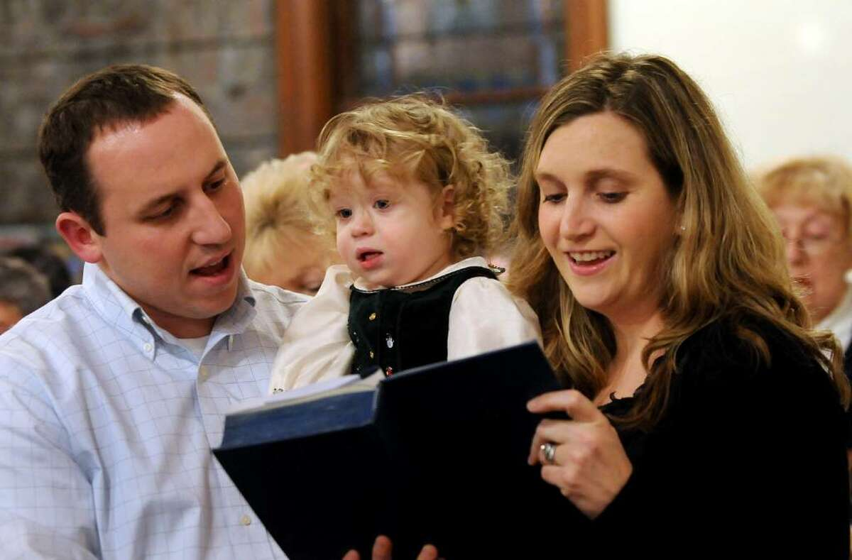 Ella DeBruin, 20 months, sings with her parents Heather and Scott during Christmas Eve mass Thursday at Hamilton Union Presbyterian Church in Guilderland. (Cindy Schultz / Times Union)