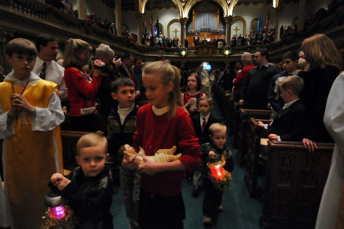 Audrey Martino of Latham, 11, carries the newborn Jesus Christ to the manger during a procession to start a Christmas Eve service at Historic St. Mary's Church in Albany on Thursday. (Philip Kamrass / Times Union)