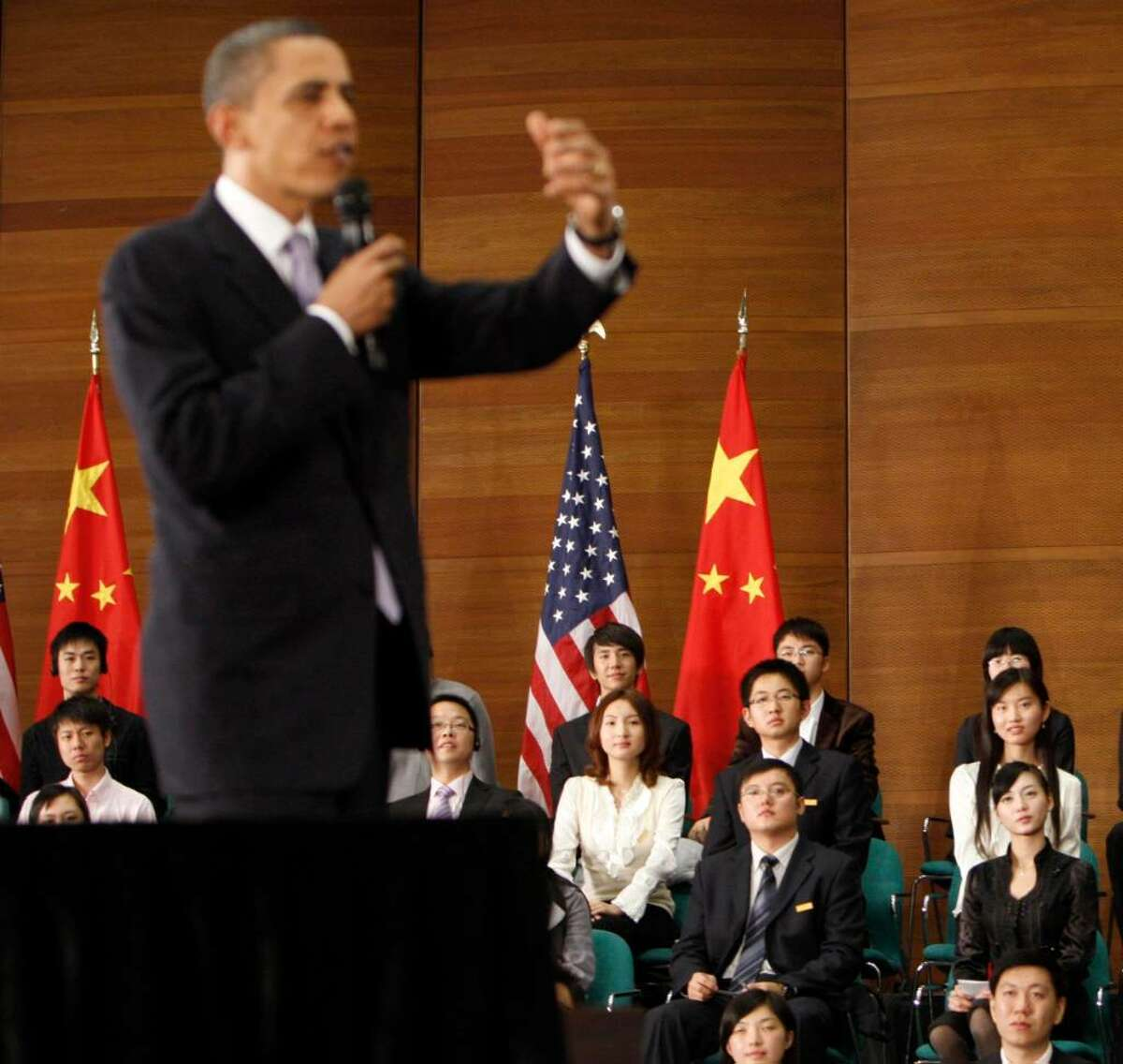File - In this Nov. 16, 2009 file photo, Wang Zifei, is seen at far right in the third row in the background while listening to President Barack Obama, left, answer questions during his town hall meeting at Shanghai Science and Technology Museum in Shanghai, China. Wang has become China's version of the