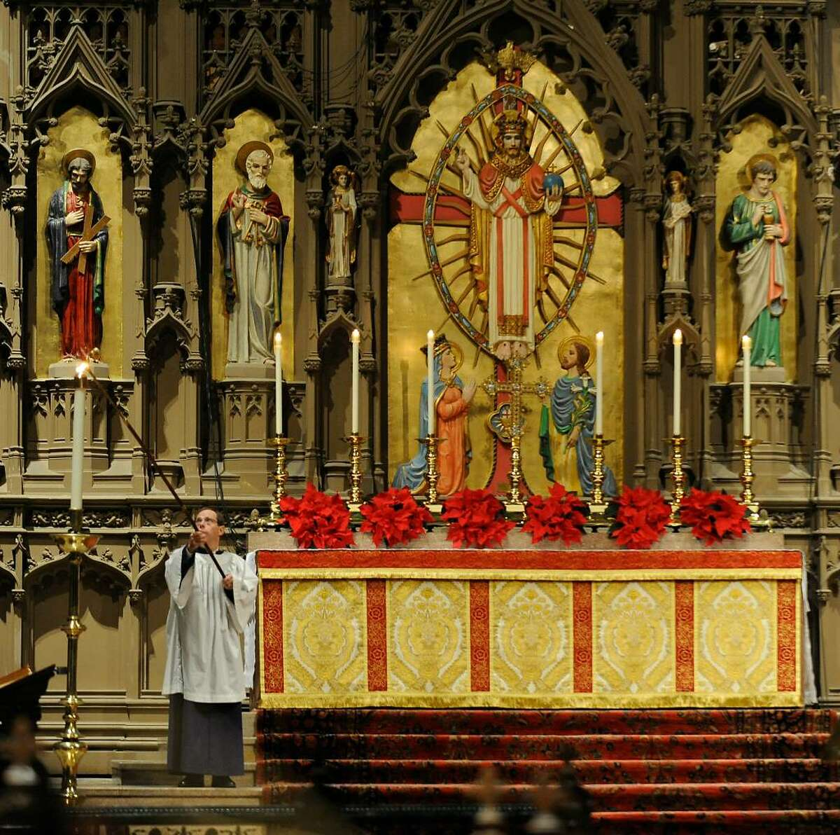 Edwin Feree lights the candles on the altar of The Catheral of All Saints on Capitol Hill in Albany in preparation for the celebration of the birth of Christ on Christmas Day. (Skip Dickstein/Times Union)