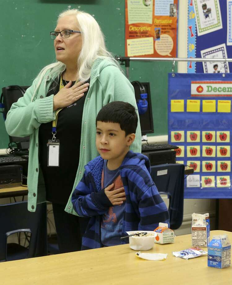 School principal Donna Finch, left, recites the pledge of allegiance during breakfast December 20 in a second grade classroom at De Zavala Elementary school on San Antonio's West Side. The San Antonio Independent School District is ranked highly statewide for its school food program, mostly due to serving breakfast in class which drives student participation rates higher. Also reciting the pledge is student Adrian Batista, 7. Photo: John Davenport /San Antonio Express-News / ©John Davenport/San Antonio Express-News