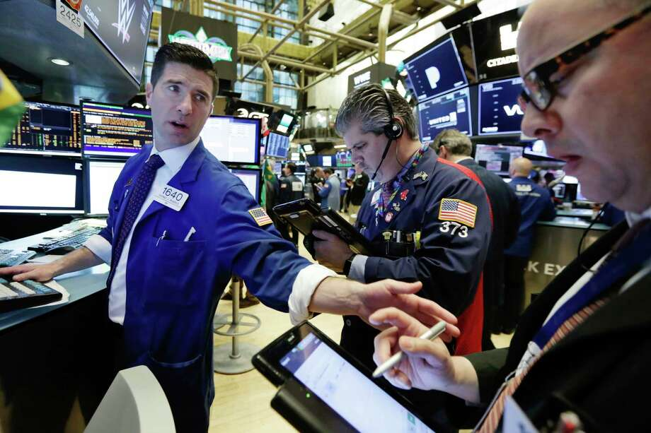 Specialist Thomas McArdle, left, works with traders John Panin, center, and Jeffrey Vazquez on the floor of the New York Stock Exchange, Monday, April 2, 2018. U.S. stocks are skidding Monday morning after China raised import duties on U.S. pork, apples and other products. (AP Photo/Richard Drew) Photo: Richard Drew / AP