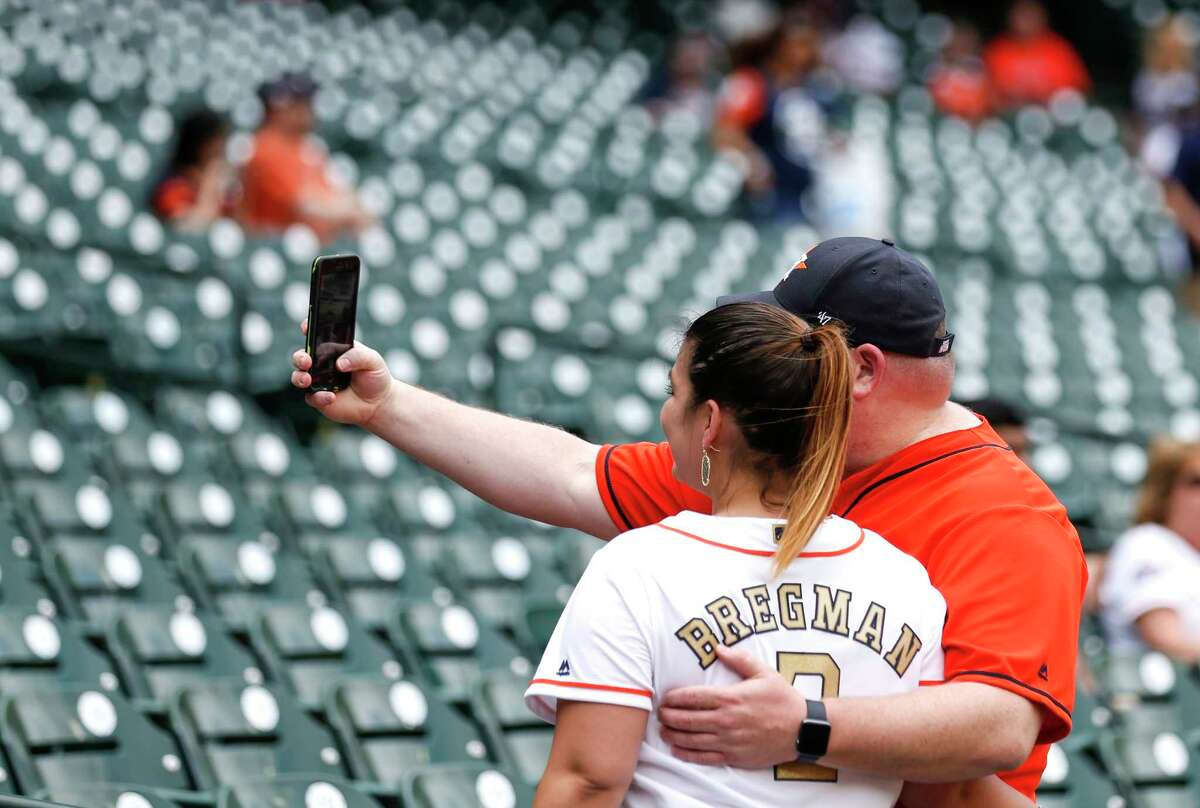 Houston Astros fans takes photos during batting practice before the Astros home opener at Minute Maid Park on Monday, April 2, 2018, in Houston.