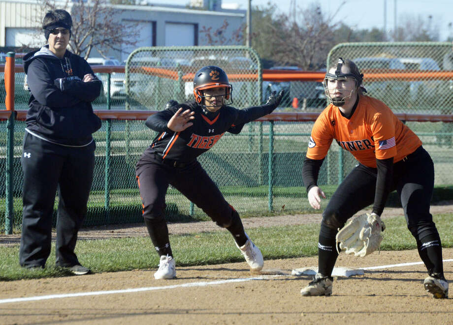 Edwardsville sophomore Maria Smith, center, jumps off third base with the delivery of the pitch during the Tigers' season opener against Gillespie.