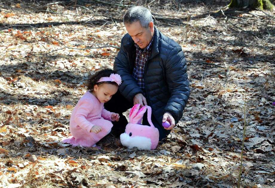 "Adriana Rocha, 2, of Milford, gets a little help filling her Easter basket by her uncle Manny Pinho during the annual Easter Egg Hunt ""Egg-Stravaganza"" at the Audubon Center at Fairfield in Fairfield, Conn., on Saturday Mar. 31, 2018. The center held two hunts during the day to accomodate the hundreds of visitors. In addition to the egg hunts, there were fun-filled familiy activities included craft making, snacks and even a visit from a very special rabbit. Photo: Christian Abraham / Hearst Connecticut Media / Connecticut Post"