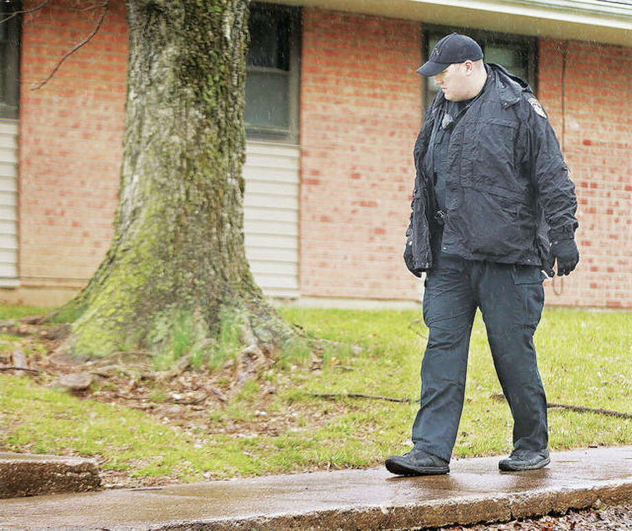Alton Police officer Brian Brenner slowly walks the sidewalk adjacent to Belle Street and Alton Acres housing complex last week, looking for shell casings or any other clues of a shooting. The shooting actually occurred south of the complex, and the shooter is still at large. The man who was shot and dropped off at OSF Saint Anthony's Hospital emergency department is recovering from his injuries. Photo: John Badman | The Telegraph