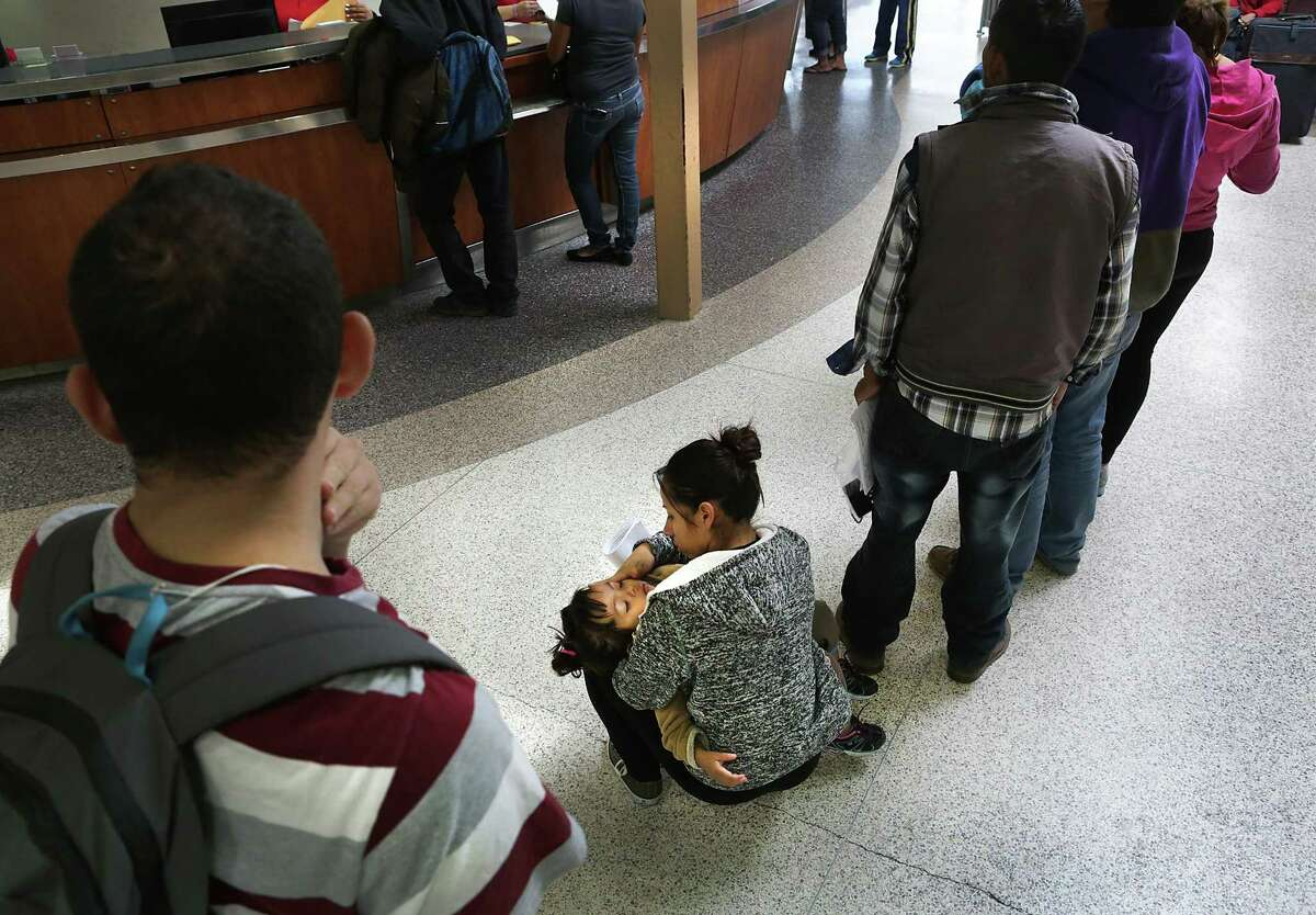 Joselin Aguilar, 23 of El Salvador, holds her sleeping daughter, Jimena Aguilar, 3, as she and other Central Americans wait in line to get their bus tickets at the McAllen, TX bus station. Aguilar was on her way to join family members in Houston, TX, on Tuesday Nov. 22, 2016.