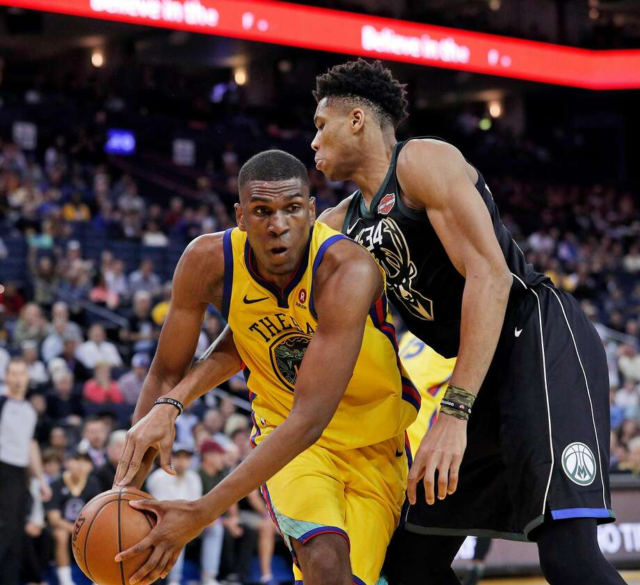 Kevon Looney (5) grabs a rebound before Giannis Antetokounmpo (34) in the second half as the Golden State Warriors played the Milwaukee Bucks at Oracle Arena in Oakland, Calif., on Thursday, March 29, 2018. Photo: Carlos Avila Gonzalez / The Chronicle