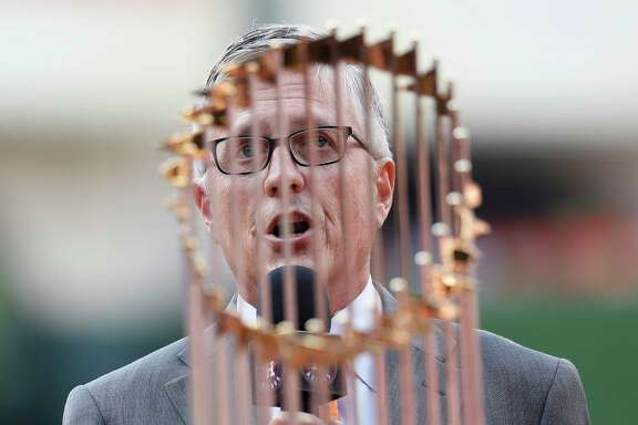 Houston Astros GM Jeff Luhnow speaks to the fans behind the World Series trophy during the pre-game ceremony before the start of the home opener during an MLB baseball game at Minute Maid Park, Monday, April 2, 2018, in Houston.